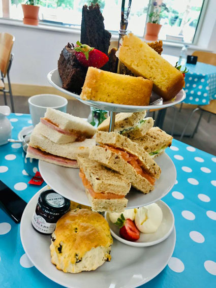 Cake stand full of cakes and sandwiches